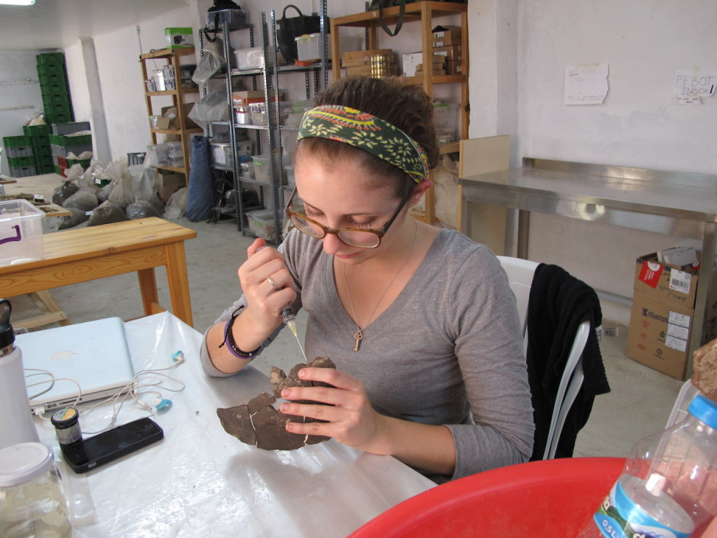 Adrienne using a syringe to consolidate a reconstructed vessel fragment with adhesive.
